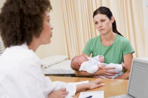woman-holding-baby-in-doctors-office